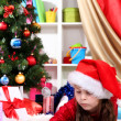 Beautiful little girl writes letter to Santa Claus in festively decorated room — Stock Photo #15315753