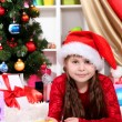 Beautiful little girl writes letter to Santa Claus in festively decorated room — Stock Photo #15315757