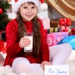 Beautiful little girl with milk and cookies for Santa Claus in festively decorated room — Stock Photo #15315767