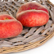 Ripe fig peaches on wicker mat isolated on white - Stock Photo