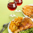 Roast chicken with french fries and cucumbers, glasses of wine on green table cloth — Stock Photo