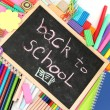 The words 'Back to School' written in chalk on the small school desk with various school supplies close-up - Stockfoto
