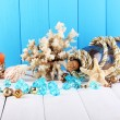 Decor of seashells on wooden table on blue wooden background — Stock Photo #15316271