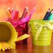 Stock Photo: Colorful pencils and felt-tip pens in pails on color background