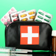First aid bag, on green background — Stock Photo