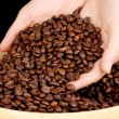 Coffee beans in hands on dark background — Stock Photo #15316877