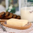 Butter on wooden holder surrounded by bread and milk on window background — Stock Photo