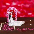 Decorative married loving couple on wooden table on red background — Foto de Stock