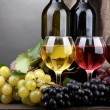 Bottles and glasses of wine and grapes on grey background — Stock Photo #15317829