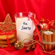 Royalty-Free Stock Photo: Cookies for Santa: Conceptual image of ginger cookies, milk and christmas decoration on red background