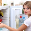 Young girl near refrigerator in kitchen — Stock Photo