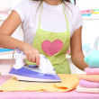 Royalty-Free Stock Photo: Young girl ironing in room