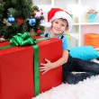 Child in Santa hat sits near Christmas tree with big gift in hands — Foto de Stock