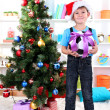 Little boy in Santa hat stands near Christmas tree with football ball — Stock Photo #15318281