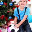 Little boy in Santa hat sits near Christmas tree with football ball — Stock Photo