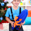 Little boy in Santa hat sits near Christmas tree with flippers — Stock Photo #15318287