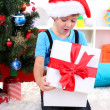 Little boy open his gifts near Christmas tree — Stock Photo #15318291