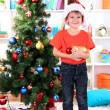 Little boy in Santa hat decorates Christmas tree in room — Stock Photo #15318293