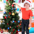 Little boy in Santa hat decorates Christmas tree in room — Stock Photo #15318297