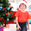 Little boy in Santa hat with milk and cookies for Santa Claus — Stock Photo #15318301