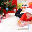 Little boy in Santa hat writes letter to Santa Claus — Stock Photo #15318331