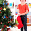 Little boy in Santa hat finds his gifts in red sock — Stock Photo #15318341