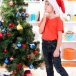 Little boy in Santa hat dreams near Christmas tree - Foto Stock