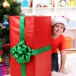Child in Santa hat near Christmas tree with big gift — Stock Photo #15318349