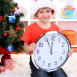 Little boy with clock in anticipation of New Year — стоковое фото #15318351