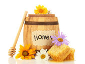 Sweet honey in barrel with honeycomb, wooden drizzler and flowers isolated on white — Stock Photo