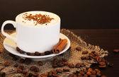Latte na dřevěný stůl na hnědé pozadí — Stock fotografie