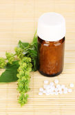Medicine bottle with tablets and flowers on bamboo mat — Стоковое фото