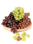 Delicious ripe pink and green grapes on wicker cradle isolated on white — Stock Photo