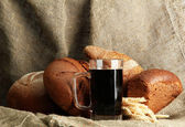 Tankard of kvass and rye breads with ears, on burlap background — Stock Photo
