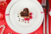 Plate with dessert in form of heart on celebratory table in honor of Valentine's Day close-up — Stock Photo