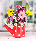 Beautiful bouquet of bright flowers in watering can on wooden table — Stockfoto