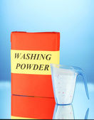 Box of washing powder with blue measuring cup, on blue background close-up — Stock Photo