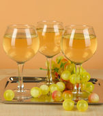 White wine in glass on salver on beige background — Stock Photo