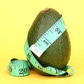 Avocado met meetlint op gele achtergrond — Stockfoto