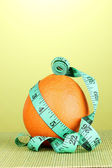 Orange with measuring tape on green background — Stock Photo