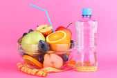 Glass bowl with fruit for diet, measuring tape and water bottle on pink background — Stock Photo