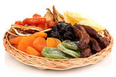 Dried fruits on wicker plate isolated on white — Stock Photo