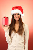 Beautiful young woman with gift, on red background — Stock Photo