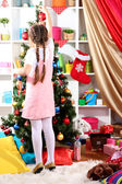 Little girl decorates Christmas tree in festively decorated room — Stok fotoğraf