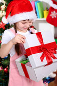 A little girl opens a gift in festively decorated room — Стоковое фото