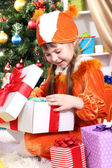 Little girl in suit of squirrels opens gift in festively decorated room — Stock Photo