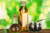 Olive oil bottle and small decanter on green background — Stock Photo