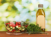 Fresh salad and oil on green background — Stock Photo