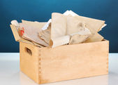 Wooden crate with papers and letters on blue background — Stock Photo