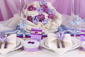 Mesa de casamento fabuloso servir na cor roxa com fundo de tecido branco e roxo — Fotografia Stock